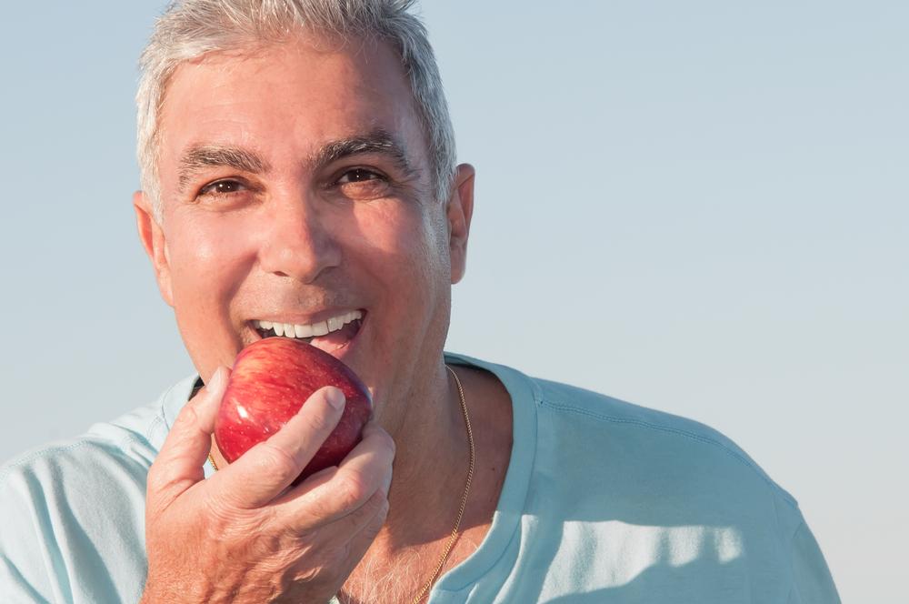 Man with healthy teeth eating an apple